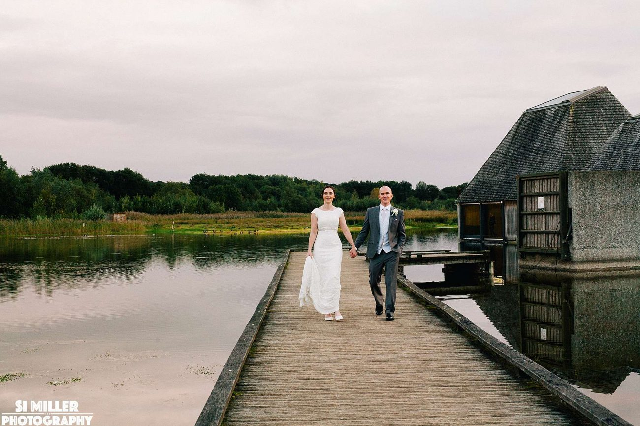 newly weds walking on jettey at brockhole nature reserve in the sunset