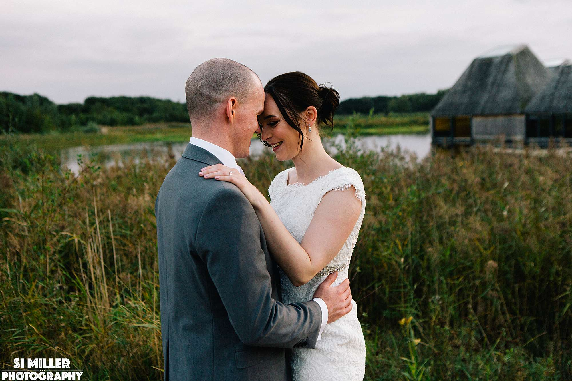Bride and groom hugging and smiling in front of reeds at brockholes