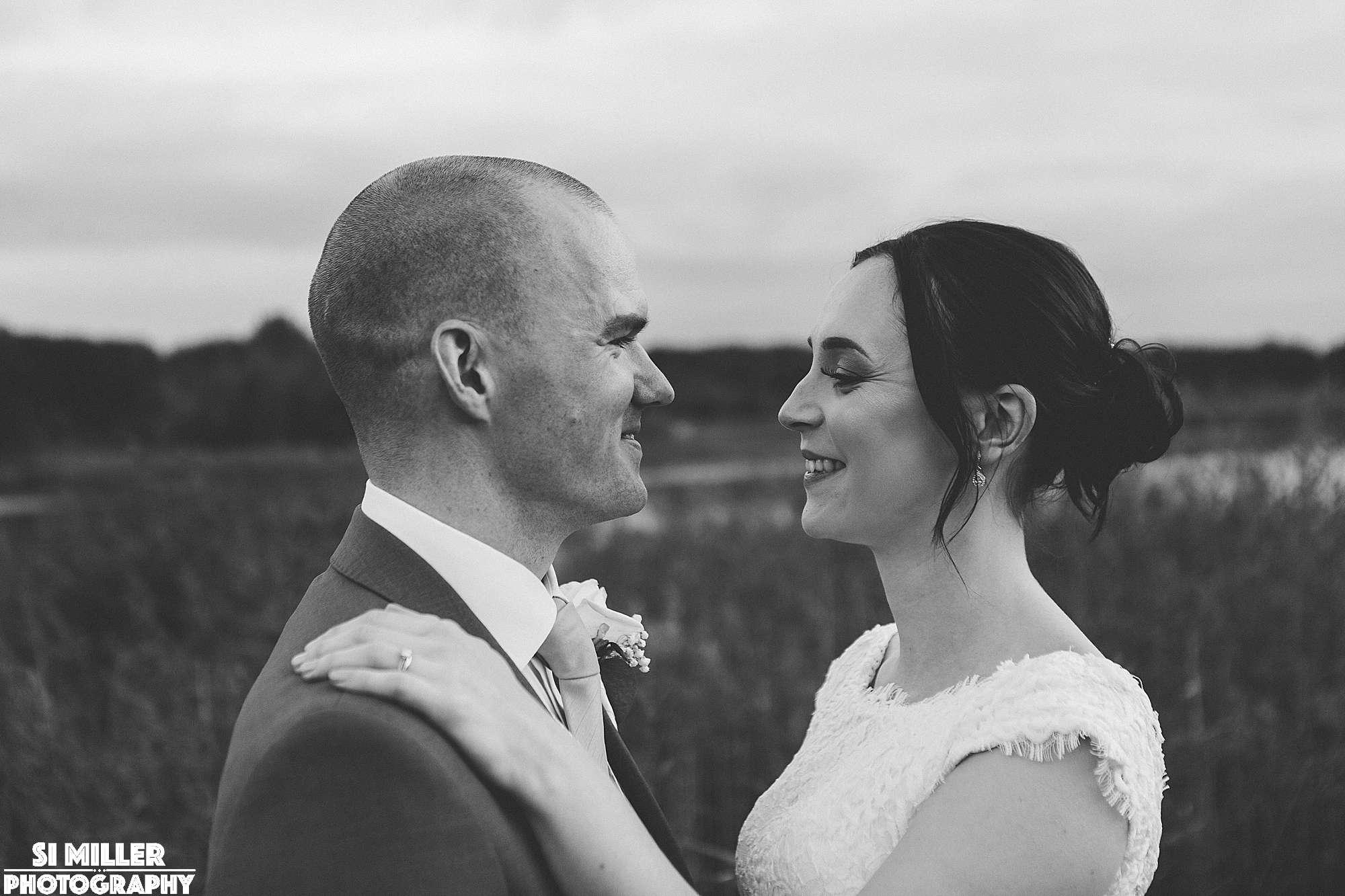 Bride with hand on grooms shoulder at brockholes