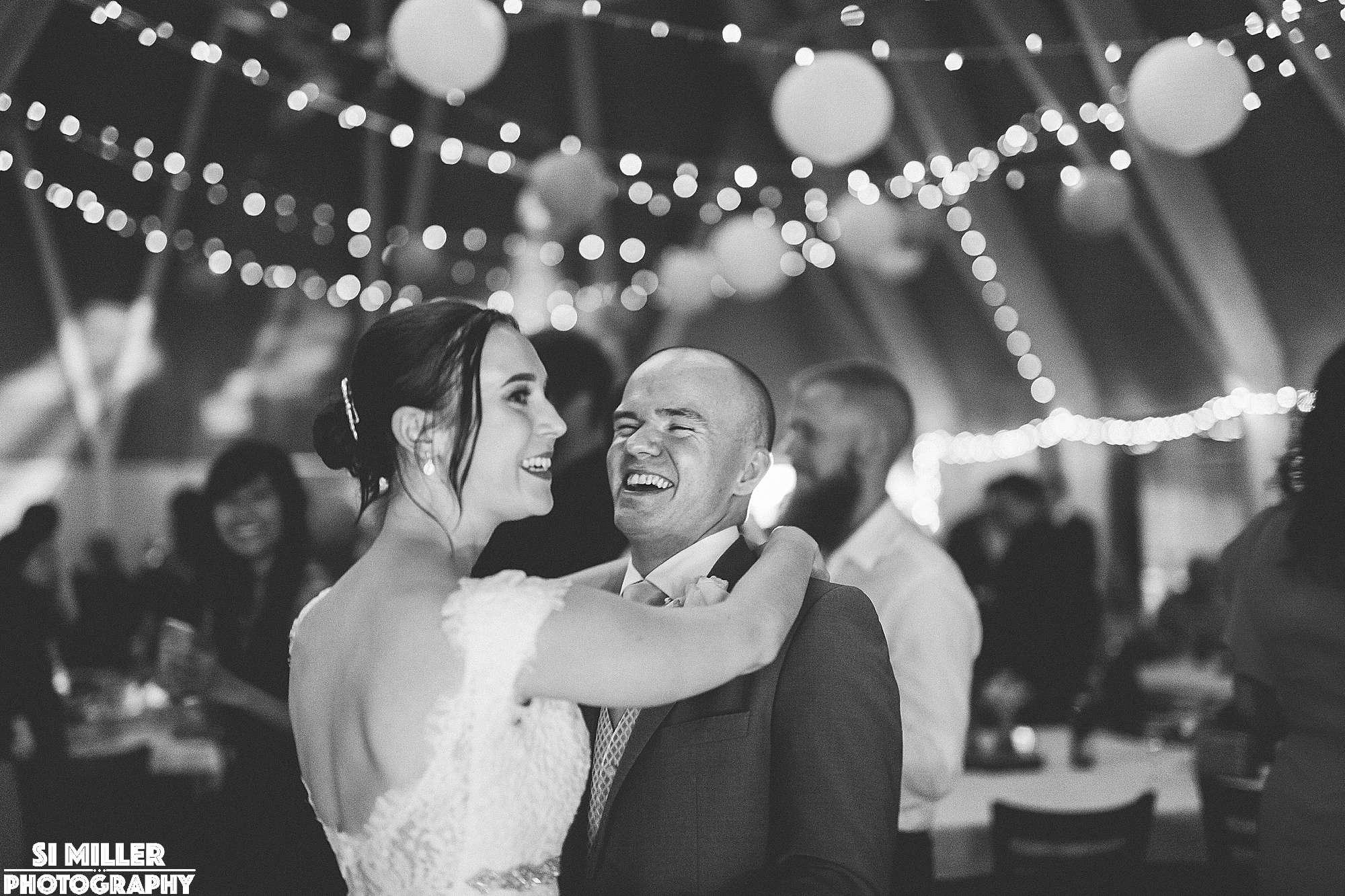 Bride and groom laughing while dancing at brockholes wedding