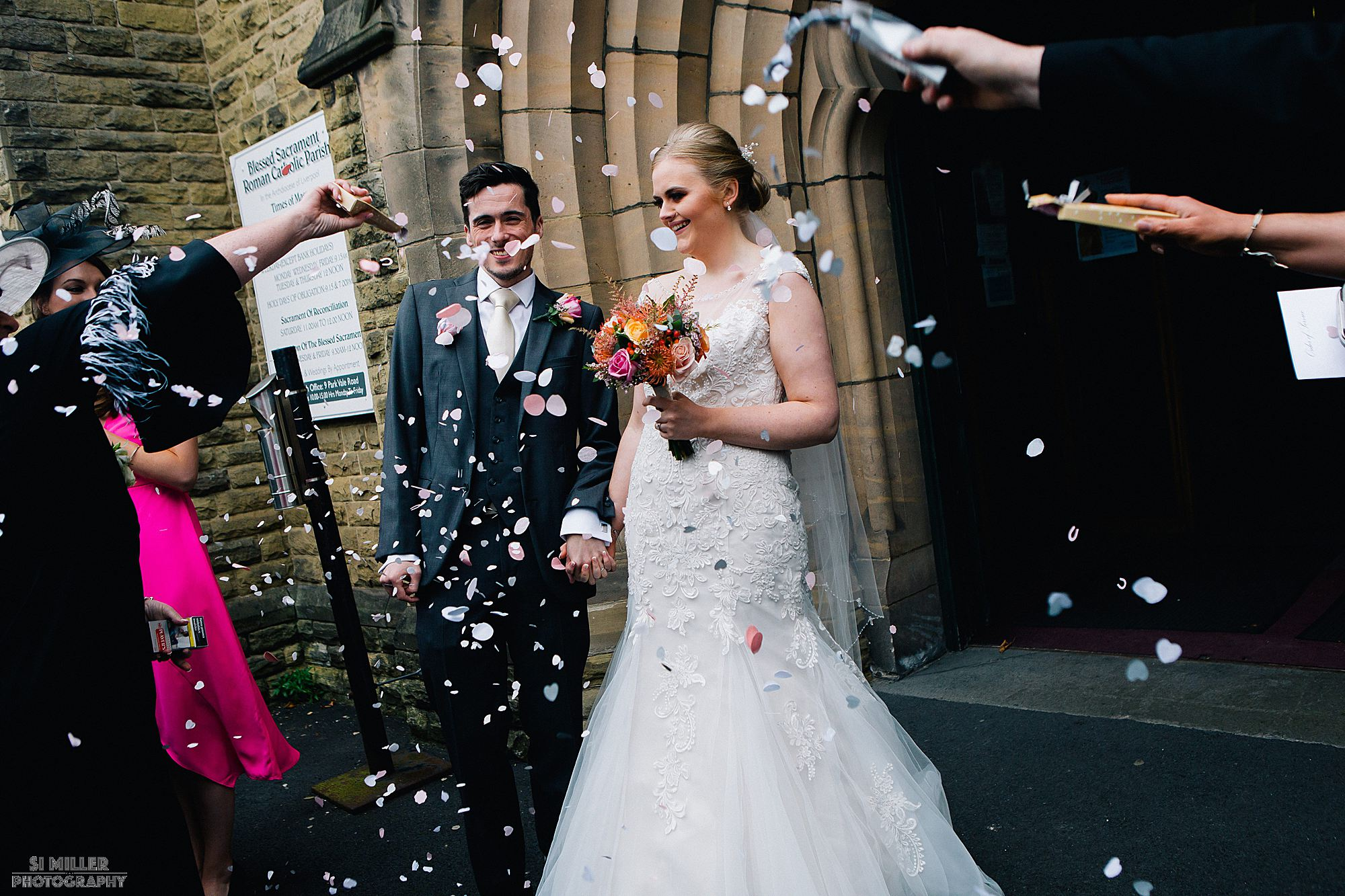 bride and groom getting confetti thrown over them