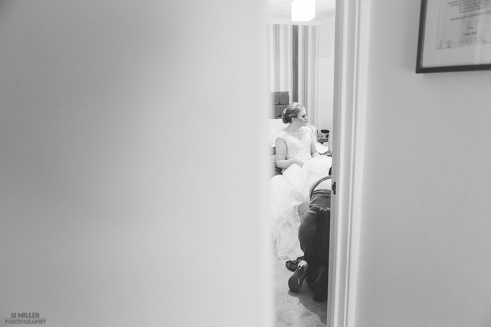 bride getting wedding dress on through bedroom door