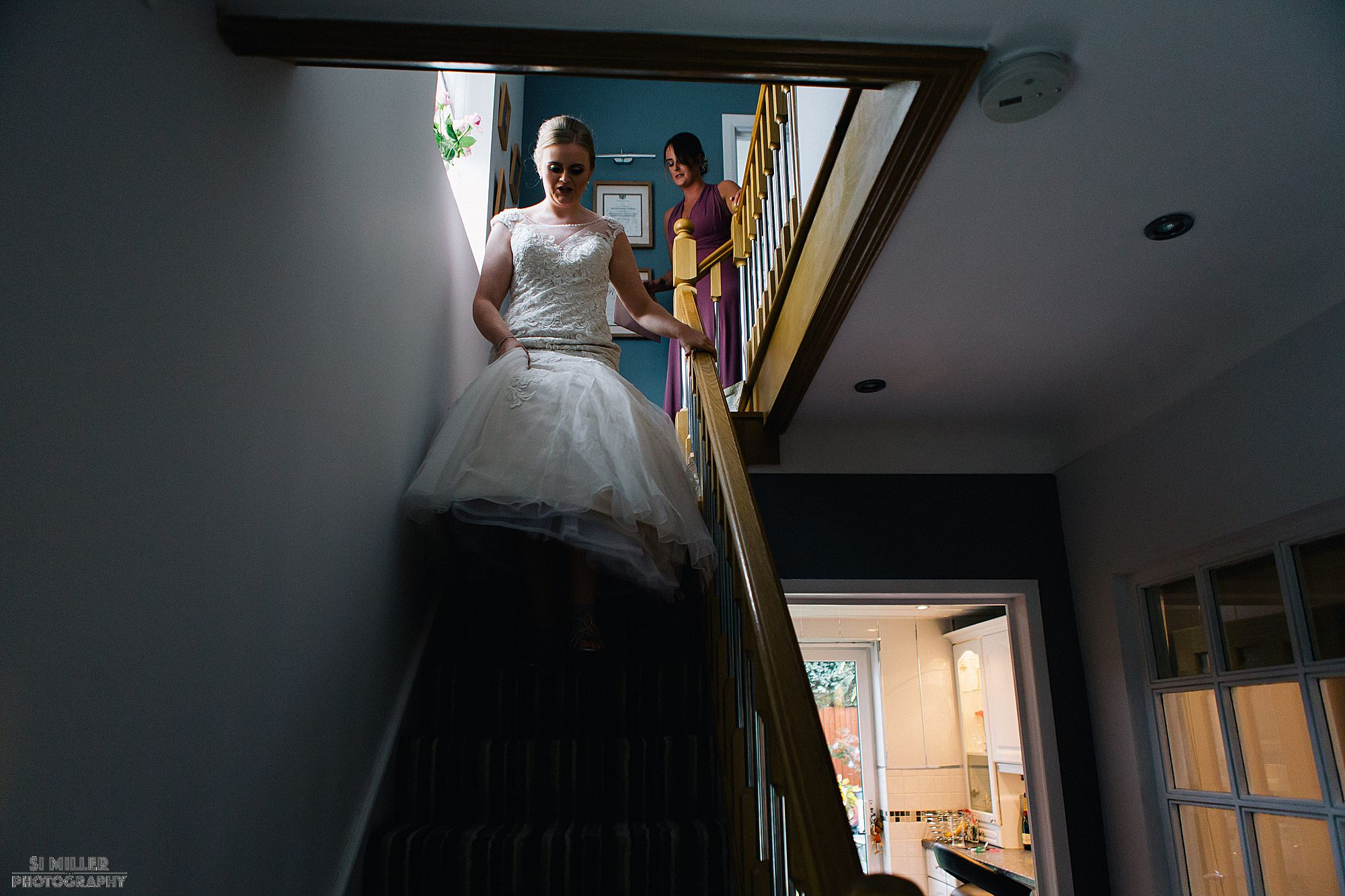 bride coming downstairs in her wedding dress