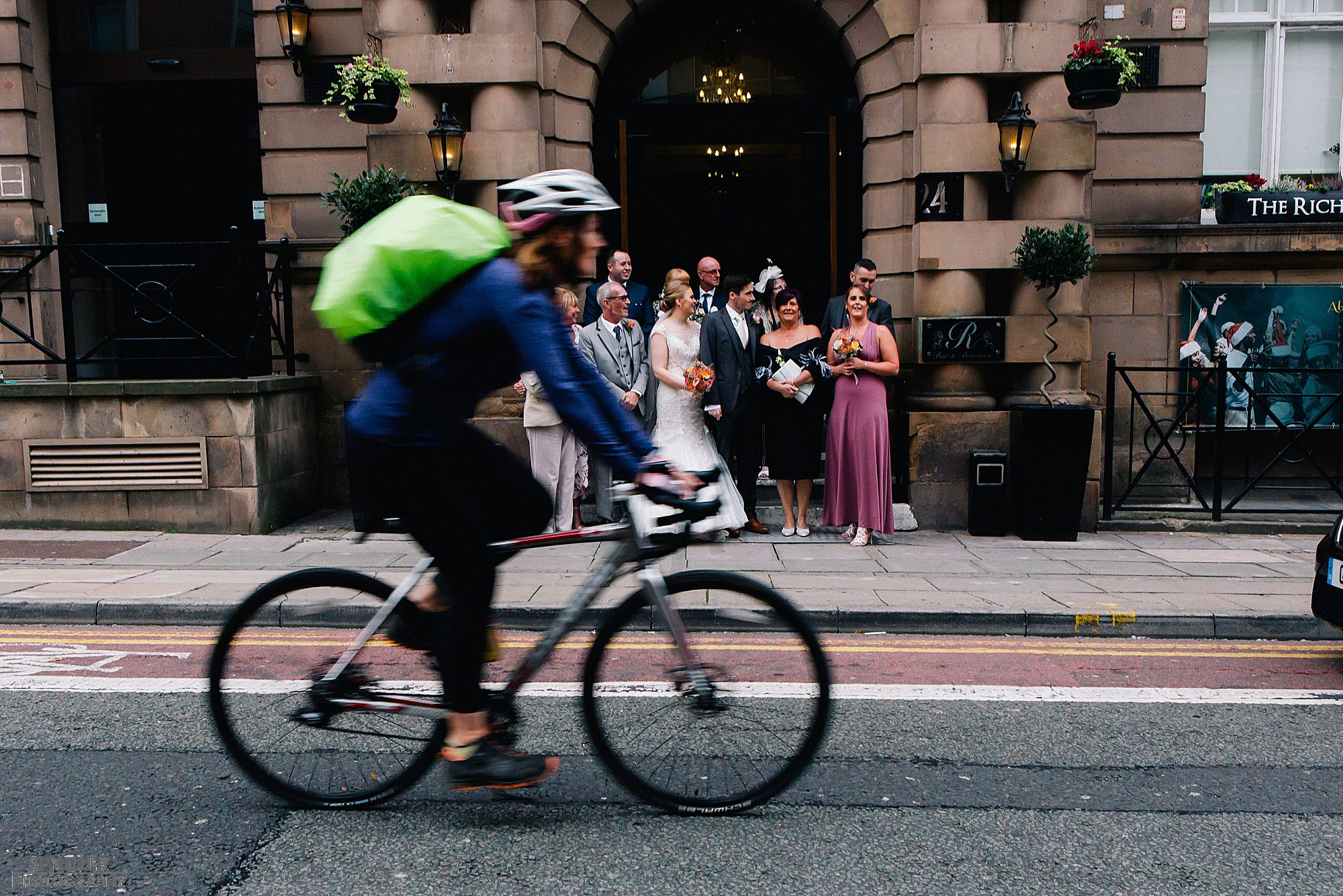 cyclist passing bridal party