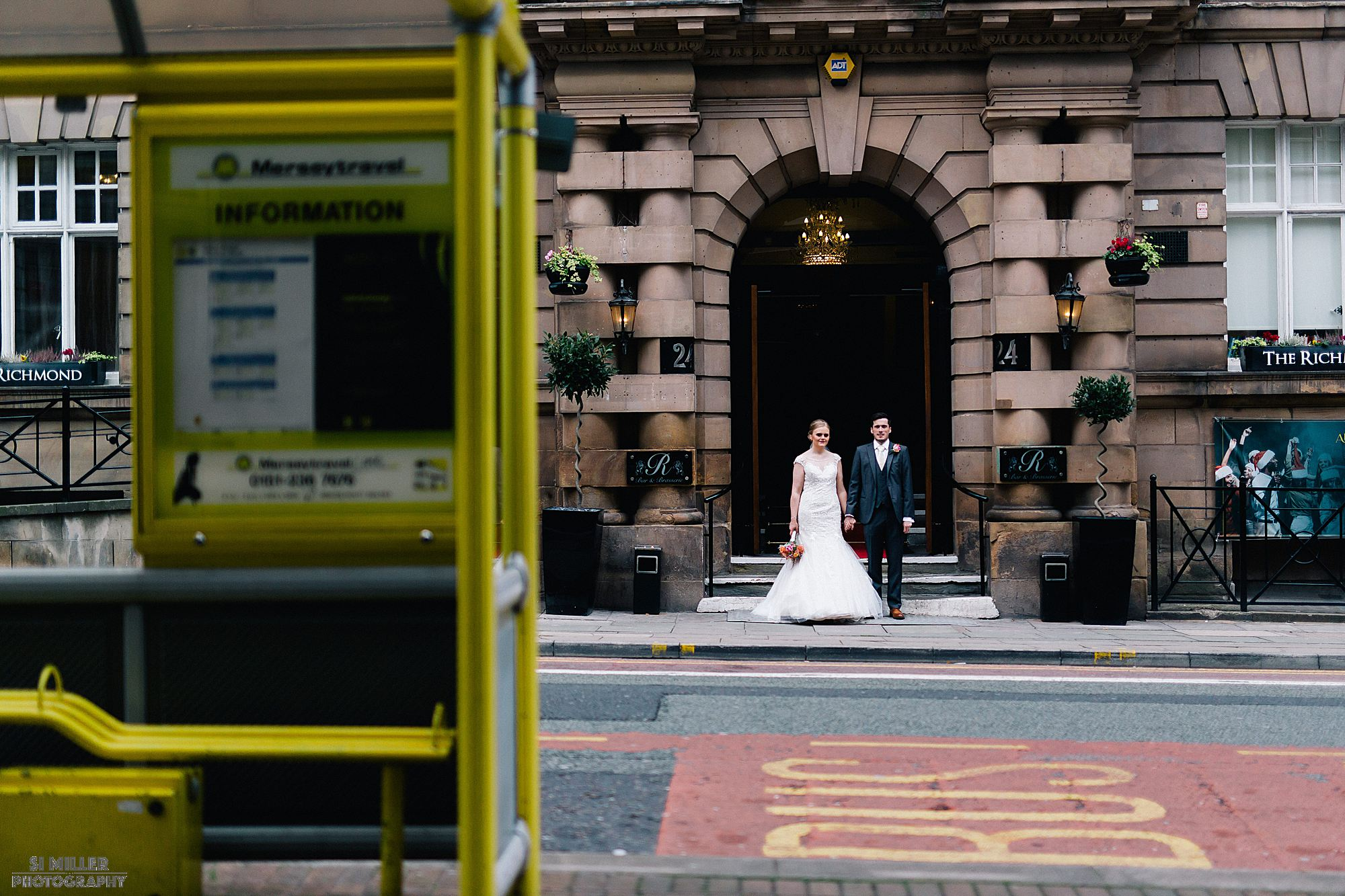 bride and groom outside Richmond Hotel with bus stop