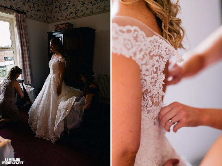 bride getting into wedding dress helped by mother