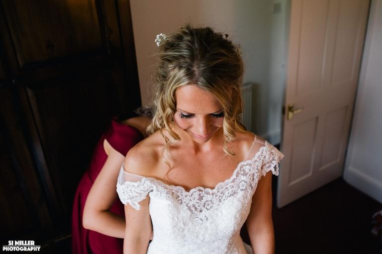 bride getting fastened into her wedding dress