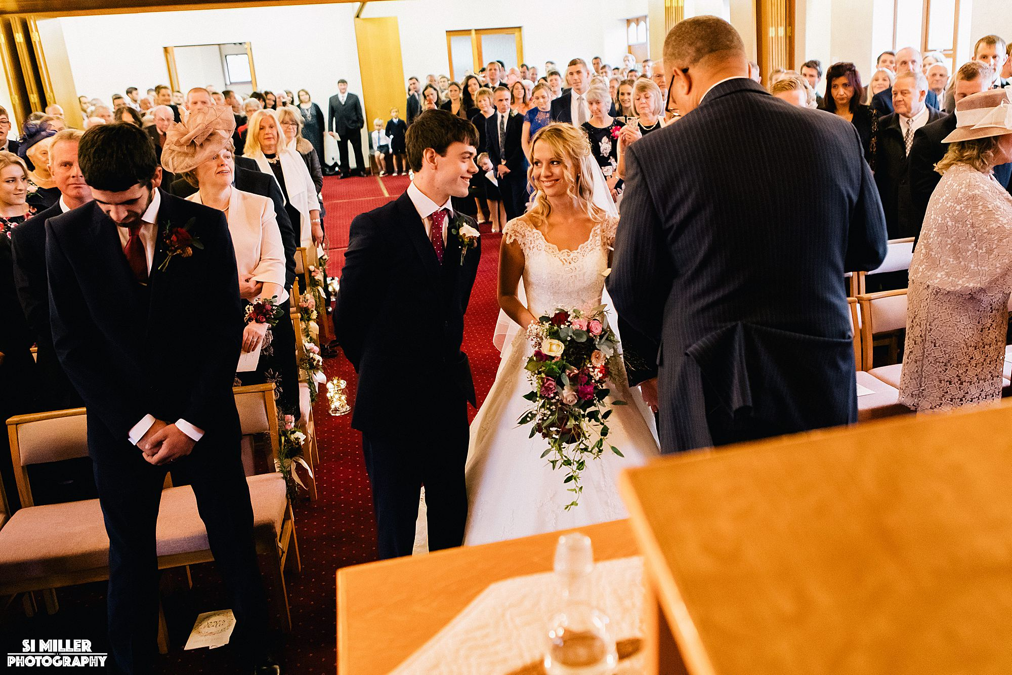 Groom and bride smiling at the alter at crown lane free methodist Preston