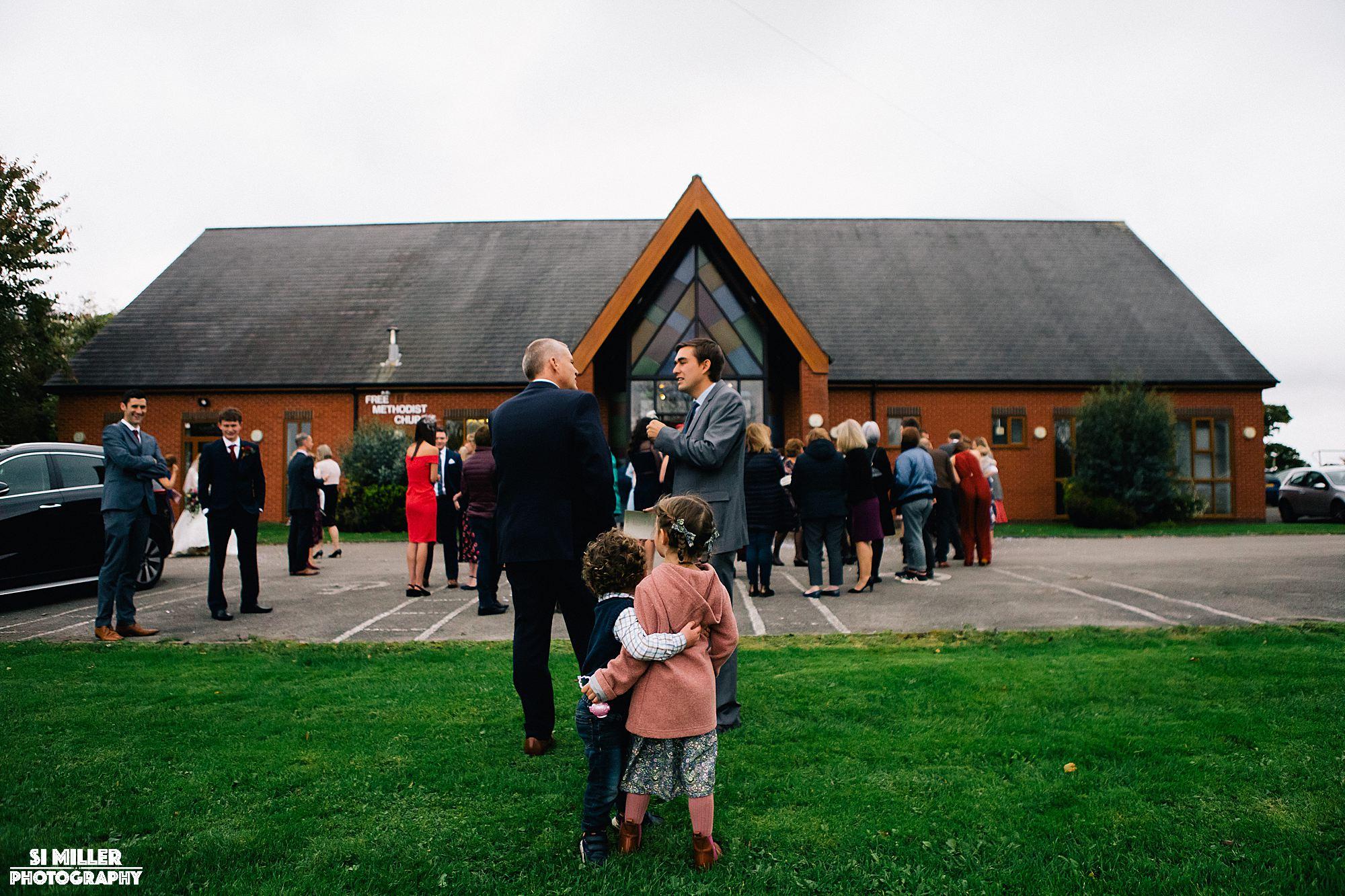 Children hugging in front of wedding guests at crown lane free methodist preston