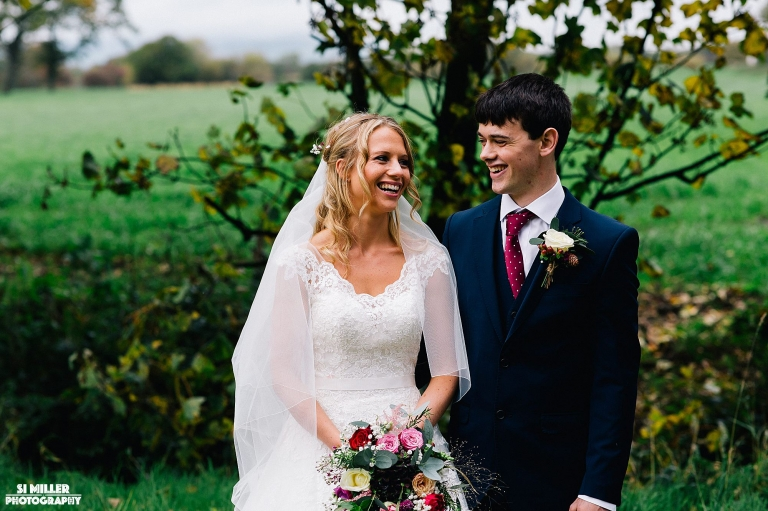 Bride and groom laughing with field behind