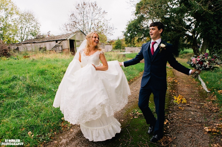 Bride and groom walking and laughing with boutique