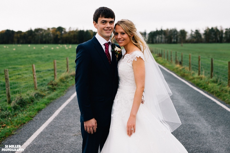 bride and groom on road leading to inn at whitewell