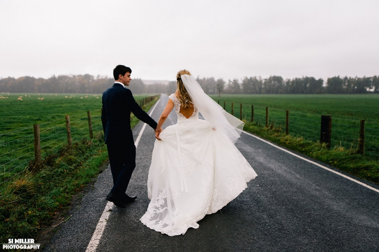 bride and groom walking on road in forrest of bowland