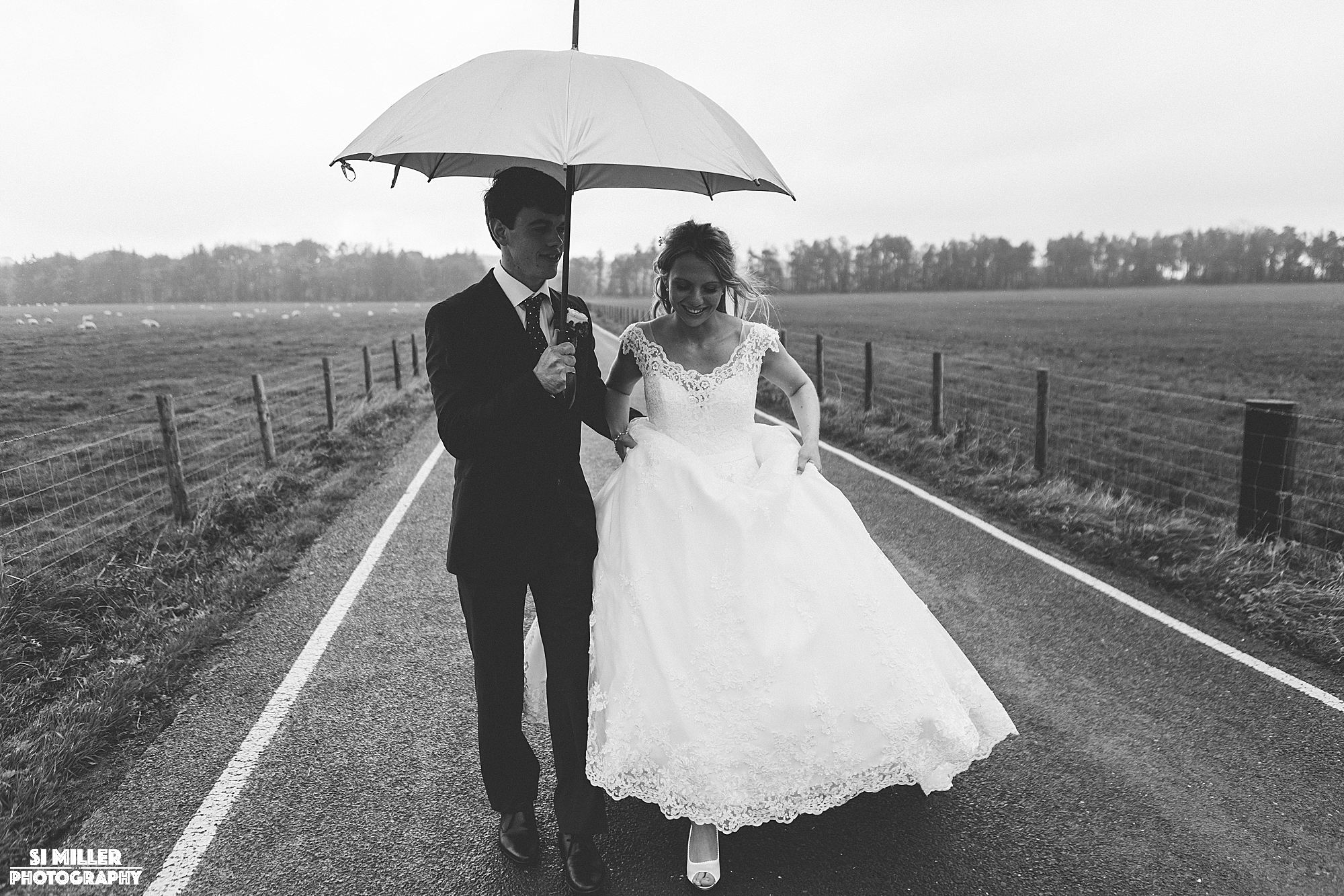 bride and groom walking on road in forrest of bowland with umbrella