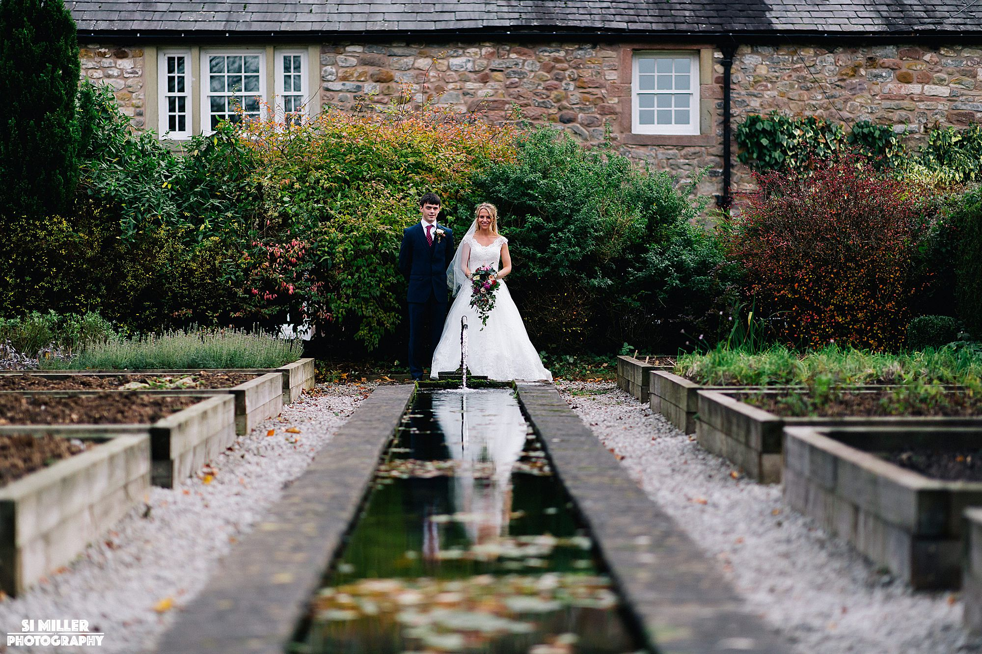Bride and groom in gardens at inn at Whitewell with reflection in water