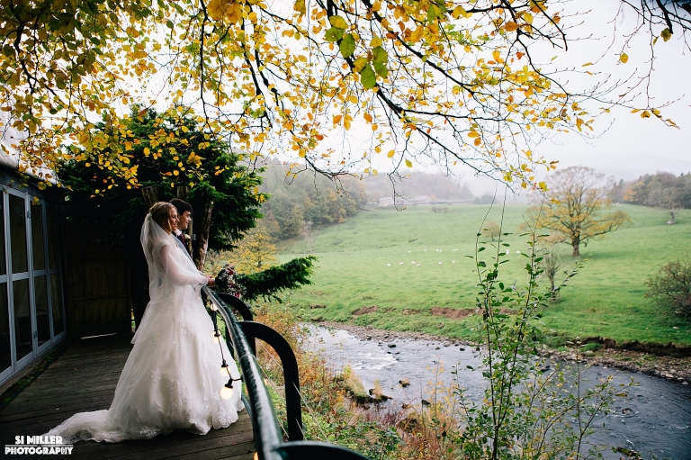 Bride in white wedding dress looking out at river ribble from Inn at Whitewell