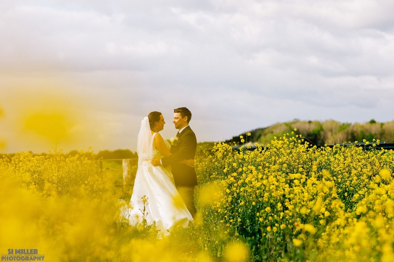 Wedding Couple in field with yellow flowers Preston wedding photographer