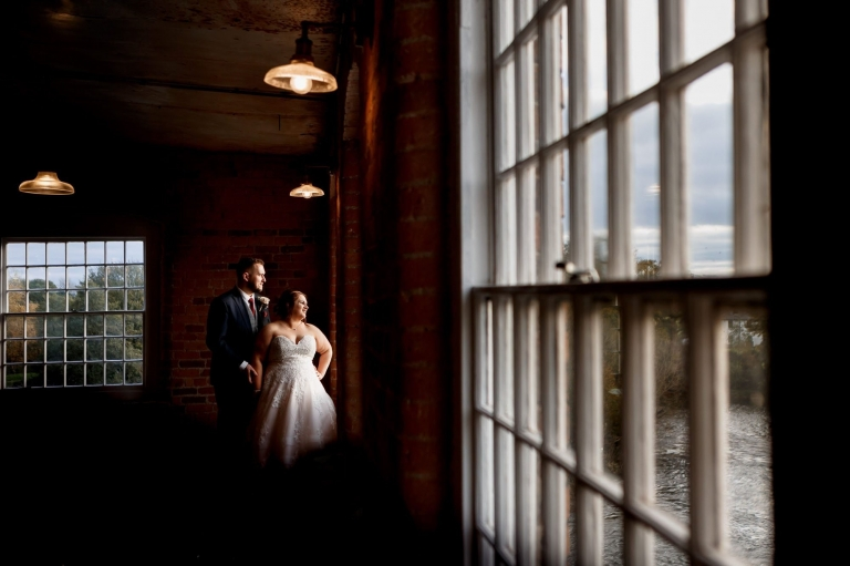 Bride and groom looking out of window at west mill derby