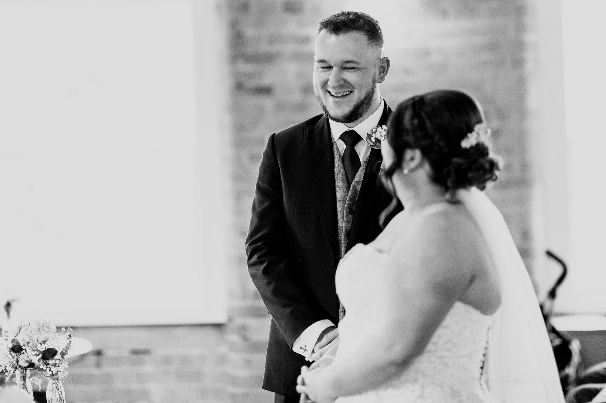 Groom laughing during wedding ceremony at the West Mill