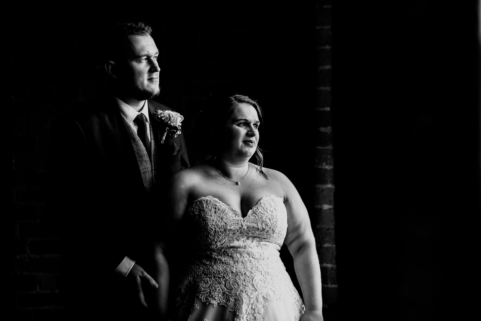 Bride and groom in front of window at west mill