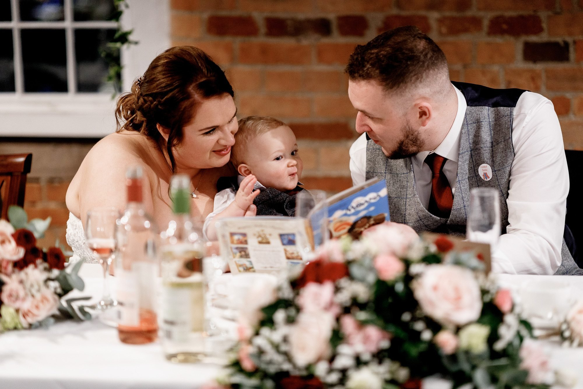 Bride and groom reading to baby son during wedding breakfast