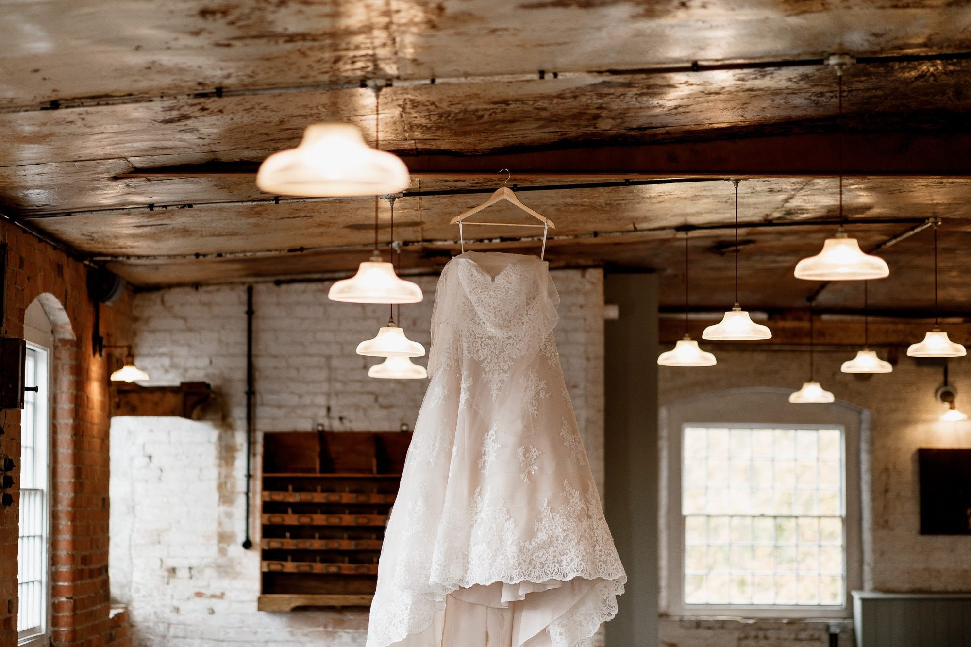 Wedding dress hanging in ceremony room at the West Mill